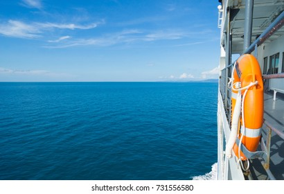 Life buoy attached to the cruise ship and blue sky and blue sea background, Life buoy on the deck of cruise ship.