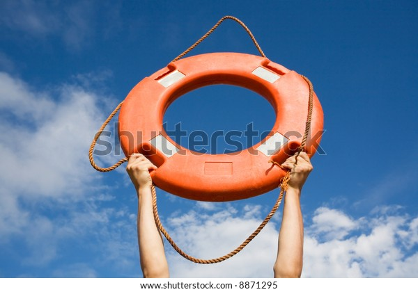 Life buoy ring in man's hands on a background of the sky.