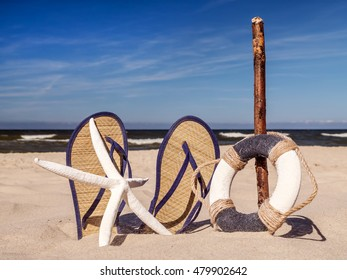 Life buoy, starfish and pair of straw flip-flops stuck into the sand against the sea and sky