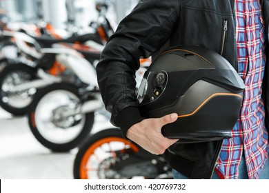 Life care. Closeup cropped shot of a male customer holding a black matte motorcycle helmet posing near a motorbike