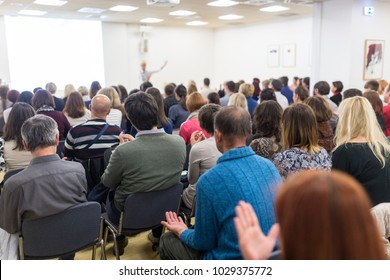 Life coaching symposium. Female speaker giving interactive motivational speech at entrepreneurship workshop. Audience in conference hall. Rear view of unrecognized participant.