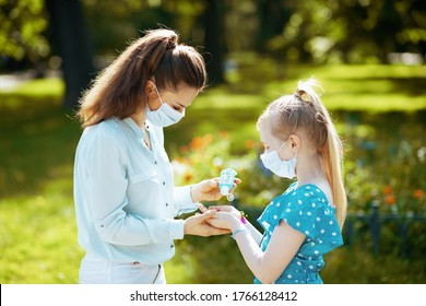 Life during coronavirus pandemic. elegant mother and daughter with medical mask disinfecting hands with sanitizer outdoors in the city park.