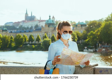 Life during coronavirus pandemic. elegant solo tourist woman in blue blouse with medical mask, sunglasses and map sightseeing outdoors on the city street.