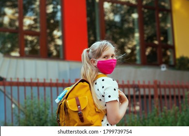 Life during coronavirus pandemic. modern pupil in white polka dot blouse with pink mask, yellow backpack and antiseptic going from school outside.