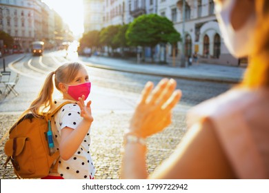 Life during covid-19 pandemic. elegant mother and child with masks and yellow backpack say goodbye before going to school outdoors.