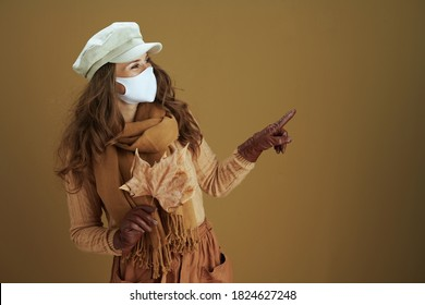 Life during covid-19 pandemic. modern 40 years old housewife in scarf with white medical mask and yellow autumn maple leaves pointing at something isolated on brown background.