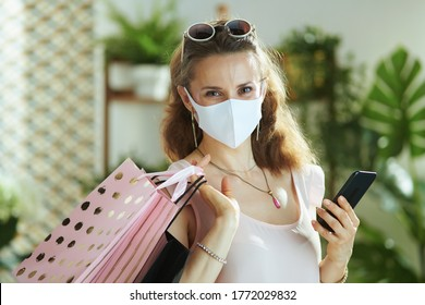 Life during covid-19 pandemic. trendy female shopper in pink blouse with medical mask, paper shopping bags and smartphone making online purchases on e-commerce website.