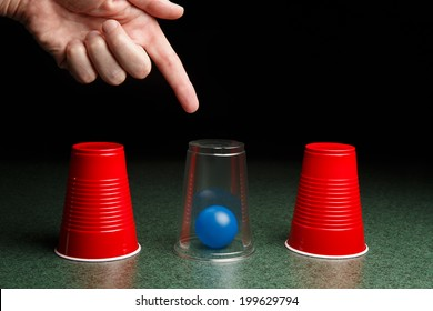Life is easy when you know the answers.  Location of blue ball is revealed by clear cup and pointing hand.  Copy space.