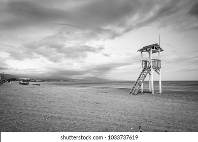 Life gaurd hut on a beach in black and white.