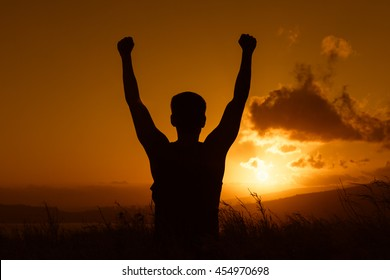 Life goals concept. Fit male holding his fist in the air against a beautiful sunset.