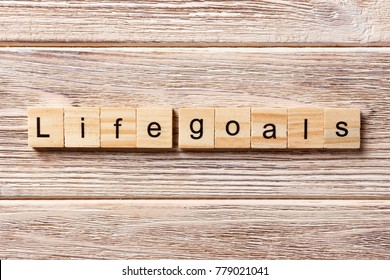 LIFE GOALS word written on wood block. LIFE GOALS text on table, concept.