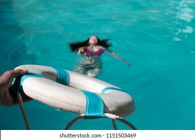 Life guard holding out life preserver to help young woman who is drowning in a swimming pool. Rescuing woman drowning in pool, focus on the life saver.