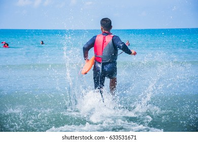 life guard wear life jacket running to help victim in the sea