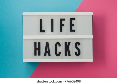 life hacks - text on a display on blue and pink bright background.