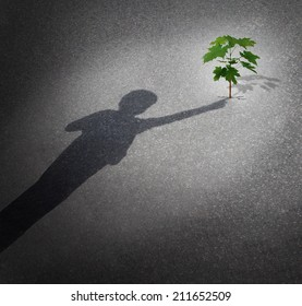 Life and hope as a grow concept with a shadow of a child touching a tree sapling growing through city pavement as an icon for the future environment protection and the support of the next generation.
