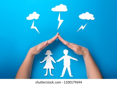 Life insurance and family health concept. Hands protect paper figures origami from lightning from the clouds on blue background. Man and woman holding hands under roof