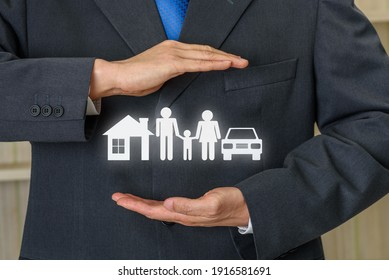 Life insurance, family protection, financial concept : Broker or insurer uses both hands to protect parents e.g. father, mother, child, a house and sedan car, depicts buying protection plan for safety