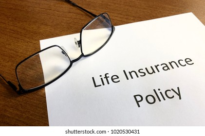Life Insurance Policy sitting on a desk with a pair of glasses.