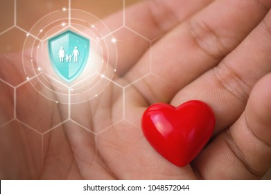 Life insurance, Shield protection family on virtual screen against Hearts in hand on backdrop, Online insurance digital technology.