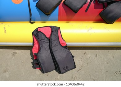 Life jacket by the side of a colorful banana boat with copy space