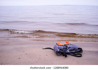 life jacket lies a sandy beach on the lake with waves