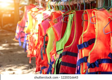 Life jacket orange color hanging on row. Life jackets, safety equipment prevent drowning. life security tool in water.