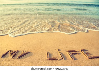 Life meditation concept. Middle age crisis, looking for porpoise, passing through life. MY LIFE is written on the sand of a beach. Temporary writing before being washed away by waves.