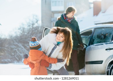 Life moment of happy family with toddler baby boy together during the winter vacations in the beautiful snow-covered city landscape with car on background.