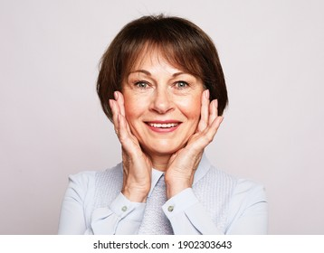Life only starts when get older. Portrait of happy and charming european senior woman with short hair laughing and amusement holding palms on cheeks over grey background