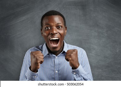 Life perception and achievement concept. Close up shot of happy successful African student or employee screaming with winning expression, fists pumped, celebrating success against blank chalkboard