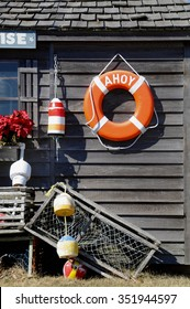 A life preserver on the wall of a shack; The outside wall of a shack decorated in a nautical theme
