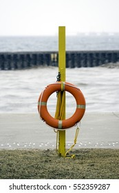 Life preserver ring hanging from yellow emergency pole on empty beach in winter