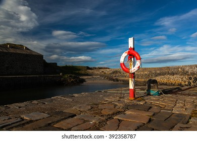 Life preserver ring on harbour/harbor wall at Portsoy in Scotland.