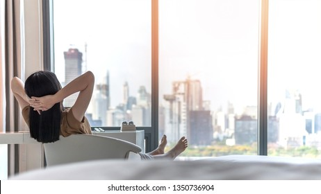 Life quality concept with young woman relaxing and resting in comfort business hotel guest room or luxury home living room looking toward beautiful city view of cityscape
