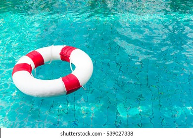 Life Ring on blue water at the swimming pool.