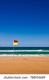A life saver flag stands alone on a beach at Gold Coast, Queensland, Australia. It's safe to swim between the flags, but the beach seems to be quite empty.