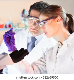 Life scientist researching in laboratory. Attractive young scientist and her post doctoral supervisor looking at the microscope slide in the forensic laboratory. Healthcare and biotechnology.