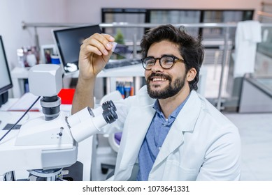 Life scientist researching in laboratory. Scientist examines biopsy samples. Satisfied male researcher smiling cheerfully while sitting at a microscope and examining a sample in his hands.