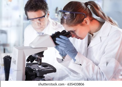 Life scientists researching in laboratory. Attractive female young scientist and her post doctoral supervisor microscoping in their working environment. Health care and biotechnology.
