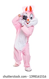 Life size easter bunny or rabbit holds photocamera, takes a pictures. Funny crazy photorapher with camera shoots easter party