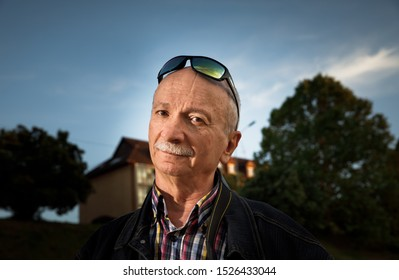 Life style concept. Old man. Portrait of a wise, skeptical and tired of life elderly man on a natural background