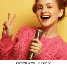 life style, happiness, emotional and people concept:   girl with a microphone singing and having fun