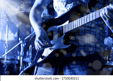 Life style image of close up young male guitarist hand, playing electric guitar