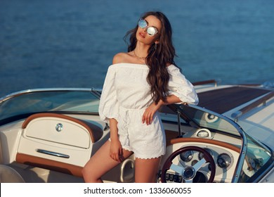 Life style portrait of young beautiful woman wearing white blouse and shorts with sunglasses standing at expensive motorboat. Wavy hair girl having fun at boat on the water