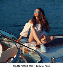 Life style portrait of young beautiful woman wearing white blouse and shorts with sunglasses sitting at expensive motorboat. Wavy hair girl having fun at boat on the water