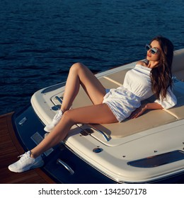 Life style portrait of young beautiful woman wearing white blouse and shorts with sunglasses lying at expensive motorboat. Wavy hair girl having fun at boat on the water
