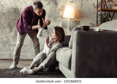 Life threatening. Short-haired woman with bruised face shutting of her furious husband while he mindlessly attacking