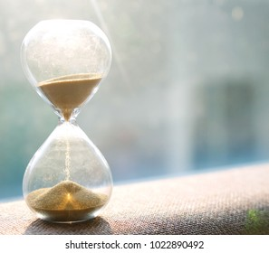 Life time passing concept. Hourglass with sunset background