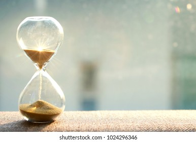 Life time passing concept. Hourglass with sun light background
