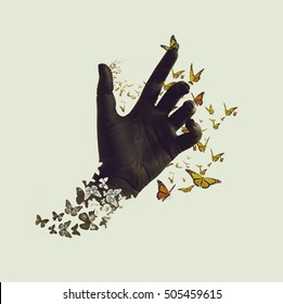 Life transformation concept image of butterflies flying out and around of black painted hand. Isolated background. Abstract symbol of freedom or dream, hope renewal and spirituality or human faith